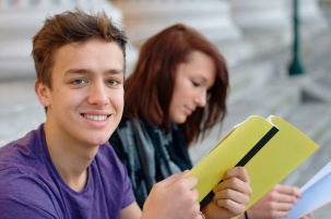Smiling teenage student outdoors with a girl at the background